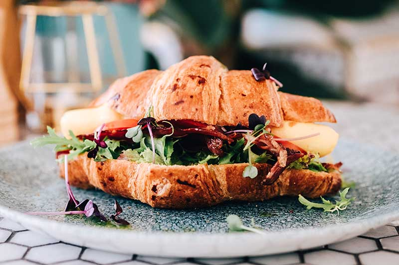 B.E.L.T – Smoked beef bacon, egg, lettuce and tomato in toasted croissant     AED 57   بي.إي.ال.تي - لحم البقر المقدد المدخن والبيض والخس والطماطم في خبز الكرواسون المحمص  57 درهمًا